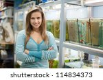 Stock photo woman near aquariums with fishes in pet shop 114834373