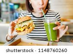 a young woman drinks green... | Shutterstock . vector #1148760260