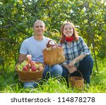Happy couple with baskets of harvested apples in garden - stock photo