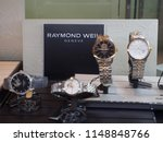 Small photo of BANGKOK, THAILAND - JULY 30, 2018: Raymond Weil, Geneve, logo in display cabinet with multiple automatic timepieces, Siam Paragon. Shallow focus. Luxury watches and fashion industry.