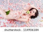 nude woman with roses eating a green apple - stock photo