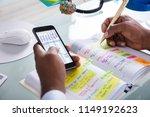 businessman holding cellphone... | Shutterstock . vector #1149192623
