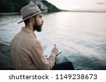 Small photo of Portrait of young bearded man writes notes in a notebook, enjoying beautiful nature and sunset. Handsome traveller wearing hipster hat sitting on the river bank. Time to travel concept.