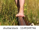 Small photo of Women`s bare feet with red nails on rails.Woman without shoes with red nails walking along the train tracks.