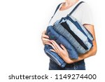 the girl holds a stack of jeans ... | Shutterstock . vector #1149274400