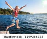 boy jumping into a beautiful... | Shutterstock . vector #1149356333