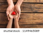 Family Holding Small Red Heart...