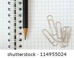 Notebook, pencil and paper clip - stock photo