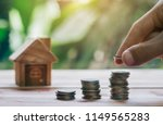 house is on wooden table. man's ... | Shutterstock . vector #1149565283