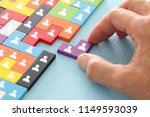 Small photo of image of tangram puzzle blocks with people icons over wooden table ,human resources and management concept