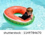 Teenaged boy floating in a swimming pool in an inflatable ring - stock photo
