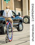 Small photo of Unique, Eclectic, Man Penny Farthing on a Patriotic High Wheel Bicycle