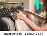 Stock photo a young woman chooses clothes on hangers in the shop store boutique showroom or shopping mall 1150341686
