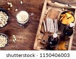 beer and snacks on wooden... | Shutterstock . vector #1150406003