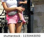 slender girl holding a baby in...   Shutterstock . vector #1150443050