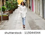 Portrait of a beautiful woman with eyes glasses walking in urban background - stock photo