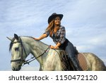 girl in plaid shirt and cowboy... | Shutterstock . vector #1150472120