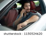 handsome man using phone while... | Shutterstock . vector #1150524620