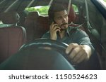 handsome man using phone while... | Shutterstock . vector #1150524623
