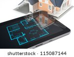 Model of the house and digital tablet with interior blueprint (corresponding with model) on screen. Architect's workplace. - stock photo