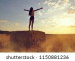 girl standing on a straw bale... | Shutterstock . vector #1150881236
