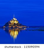 Le Mont Saint Michel, an UNESCO world heritage site in France, with reflection in the evening - stock photo