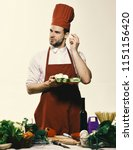 cook stands by table with... | Shutterstock . vector #1151156420