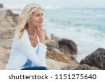 woman sitting on rocks at the... | Shutterstock . vector #1151275640