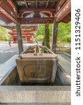 Small photo of Tokyo, Bunkyo Ward - August 6, 2018 : Wide angle view of Hishaku dippers and carved Swastika cross of Chozuya or Temizuya water ablution pavilion at Nezu Jinja Shinto Shrine