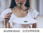 young thin girl eat cucumber.... | Shutterstock . vector #1151496536