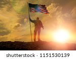 Silhouette of man holding US flag American on the mountain. The concept of Independence Day. a successful silhouette winner, a man waving an American flag on top of a mountain peak - stock photo