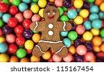 christmas gingerbread man sleeping on gum balls bed - stock photo