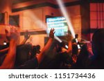 Small photo of blurred of christian congregation worshiping God in big church hall in front of music stage