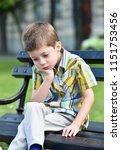 sad child boy sitting on a bench   Shutterstock . vector #1151753456
