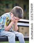 sad child boy sitting on a bench   Shutterstock . vector #1151753459