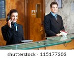 Stock photo profile shot of attractive executives at the reception of a hotel woman attending phone call 115177303