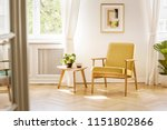 Stock photo a retro yellow armchair and a wooden table in a beautiful sunny living room interior with 1151802866