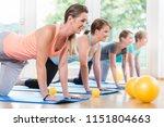 Small photo of Happy moms in postnatal regression course doing yoga asana