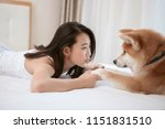 Stock photo young asian woman lying on bed playing with pet dog 1151831510