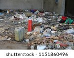 Small photo of rags and garbage in an illegal shelter for illegal immigrants discovered by the police with an old red fire extinguisher and many polluting waste