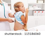 Little girl coughing at the doctor checkup - a health professional consulting her - stock photo