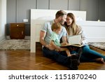 young parents reading book to... | Shutterstock . vector #1151870240