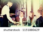 smiling waiter serving guests... | Shutterstock . vector #1151880629