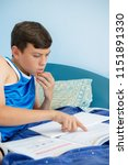 Caucasian teenage boy laying on his bed reading a textbook - stock photo
