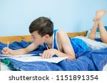 Teen boy doing homework on his bed - stock photo