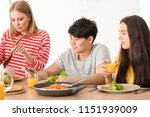 friends eating at table in... | Shutterstock . vector #1151939009