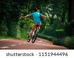 woman riding a bike on sunny... | Shutterstock . vector #1151944496