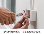 The technician is using a pliers wrench to install the power plug on the wall. - stock photo
