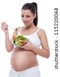 young pregnant woman eating healthy vegetable salad, healthy nutrition and pregnancy - stock photo