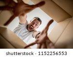 the surprised man unpacking ... | Shutterstock . vector #1152256553